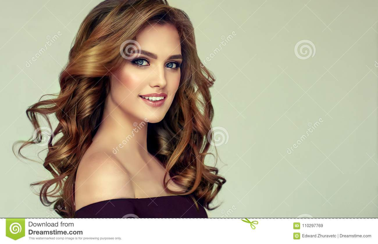 Brown haired woman with voluminous, shiny and curly hairstyle. Frizzy hair.