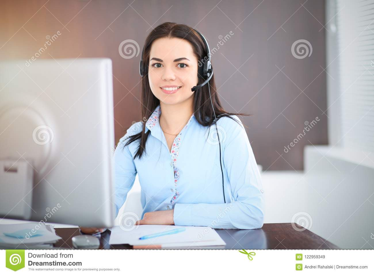 Young brunette business woman looks like a student girl working in office. Hispanic or latin american girl talking by