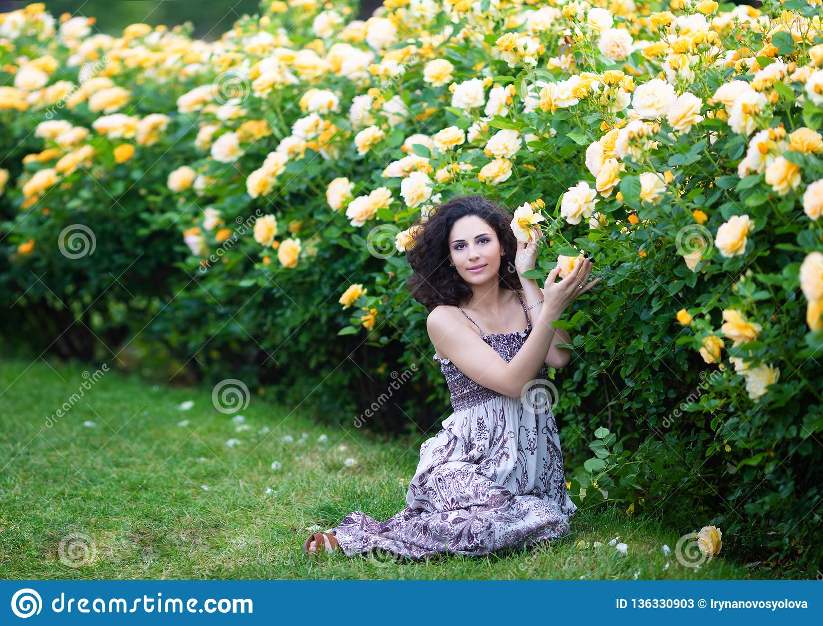 Young brunette Caucasian woman with curly hair sitting on green grass near yellow roses Bush in a garden, looking straight to the