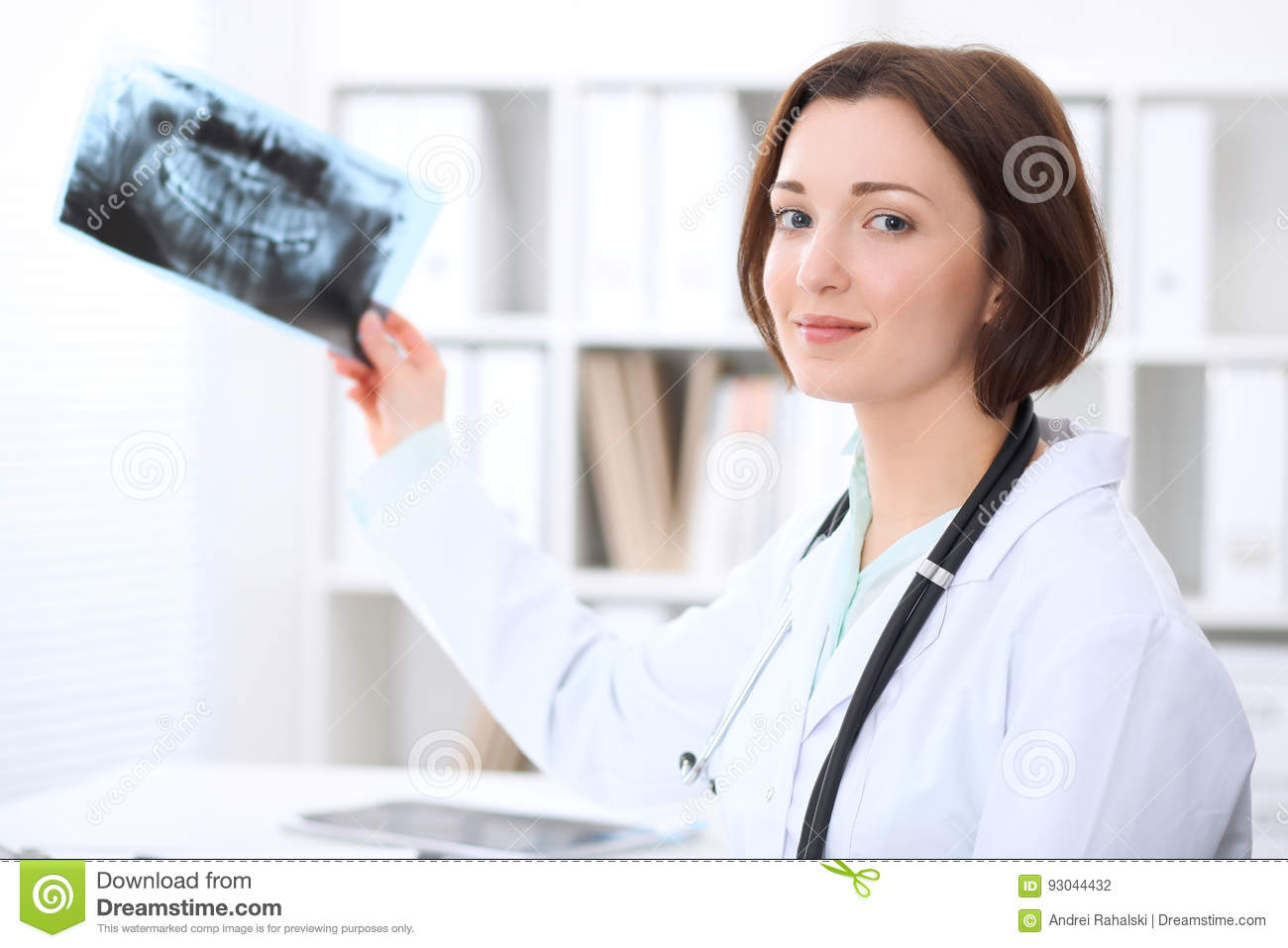 Young brunette female dentist sitting at the table and examines dental X-ray