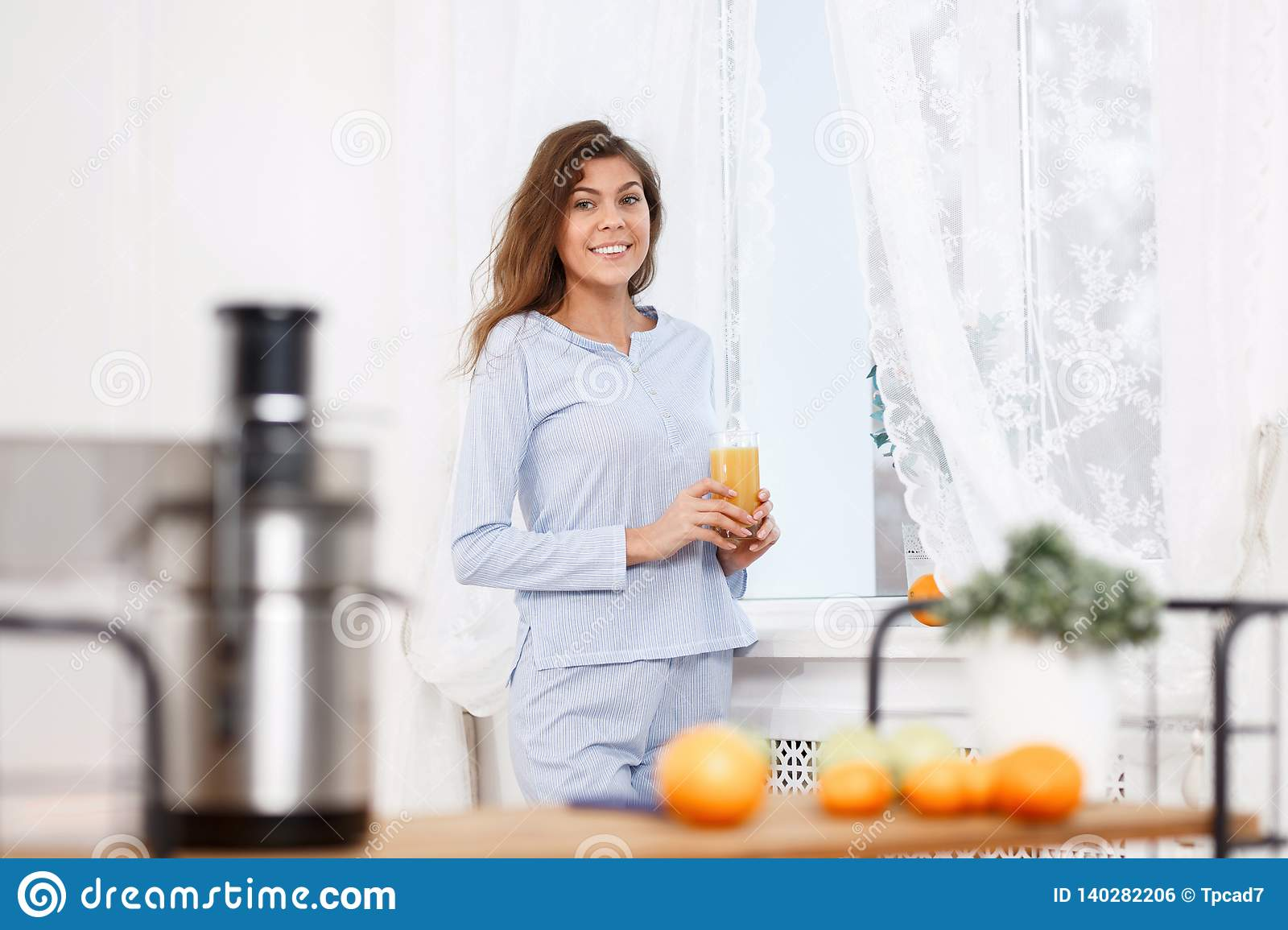Young brunette girl dressed in the light-blue pajama stands with glass of fresh juice next to the window in the light