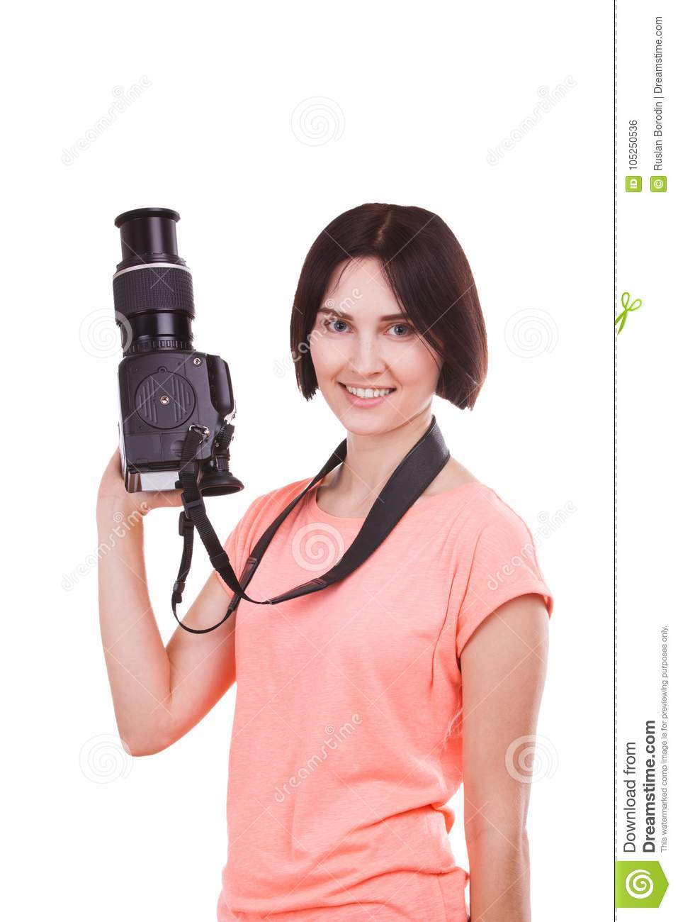 A girl is holding a camera in her hand and looking to the side on a white background