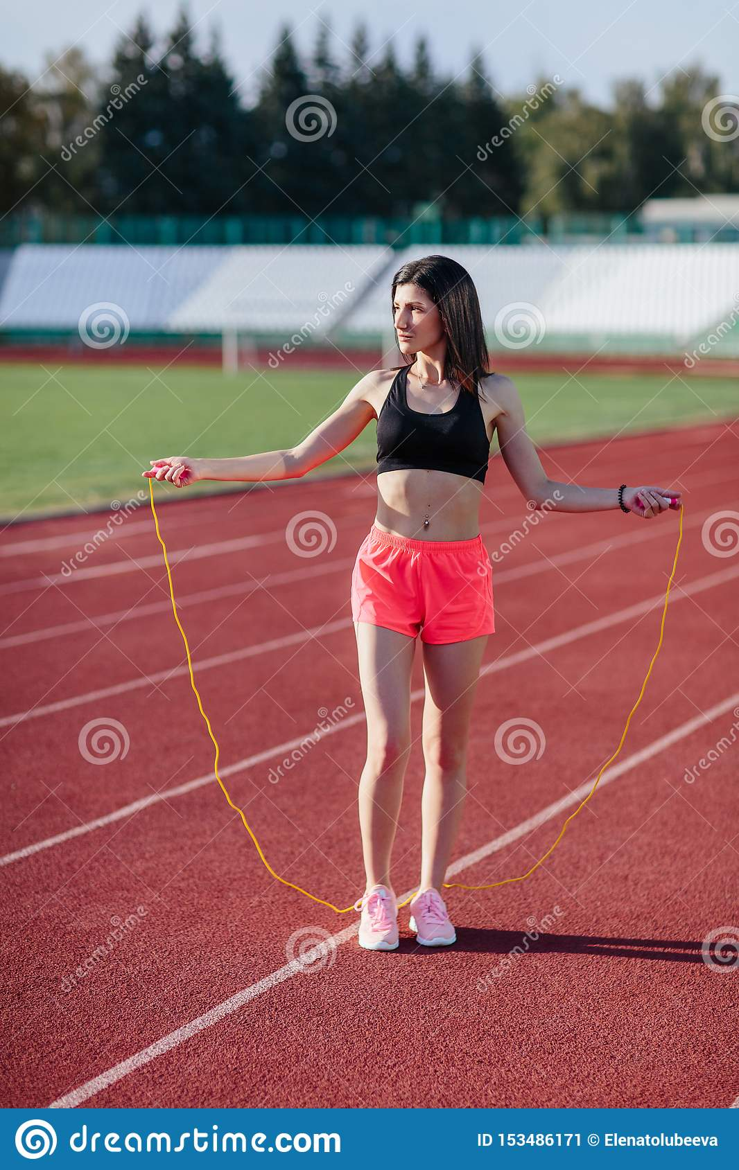 Young brunette woman athlete in pink shorts and black top on stadium sporty lifestyle standing on track holding jump rope under