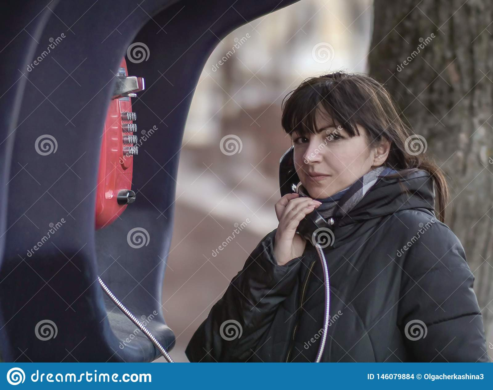 Young brunette woman calling from a red street payphone, looking directly at the camera