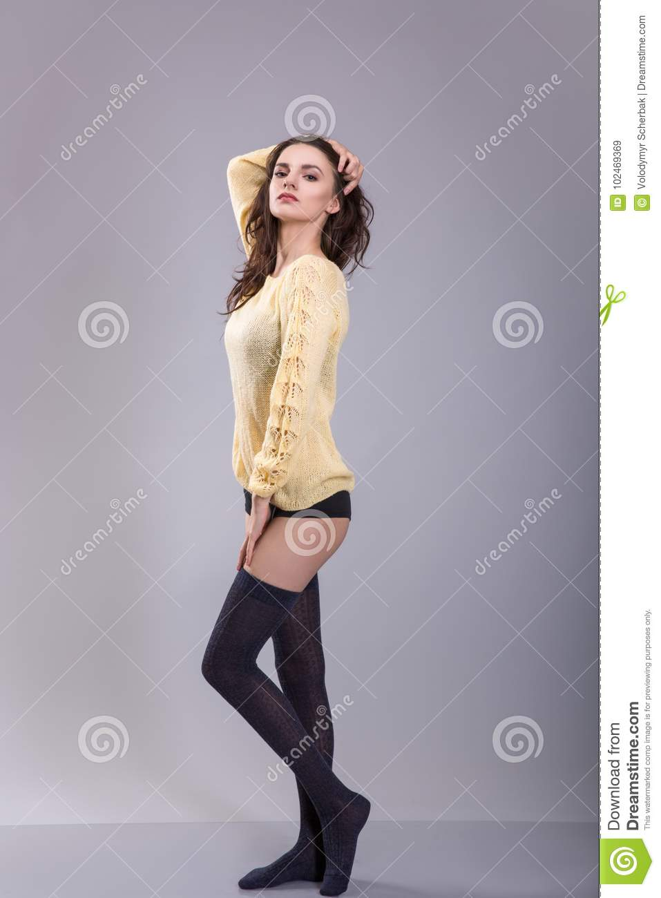 Young woman in knitted jumper and stockings stands on gray background