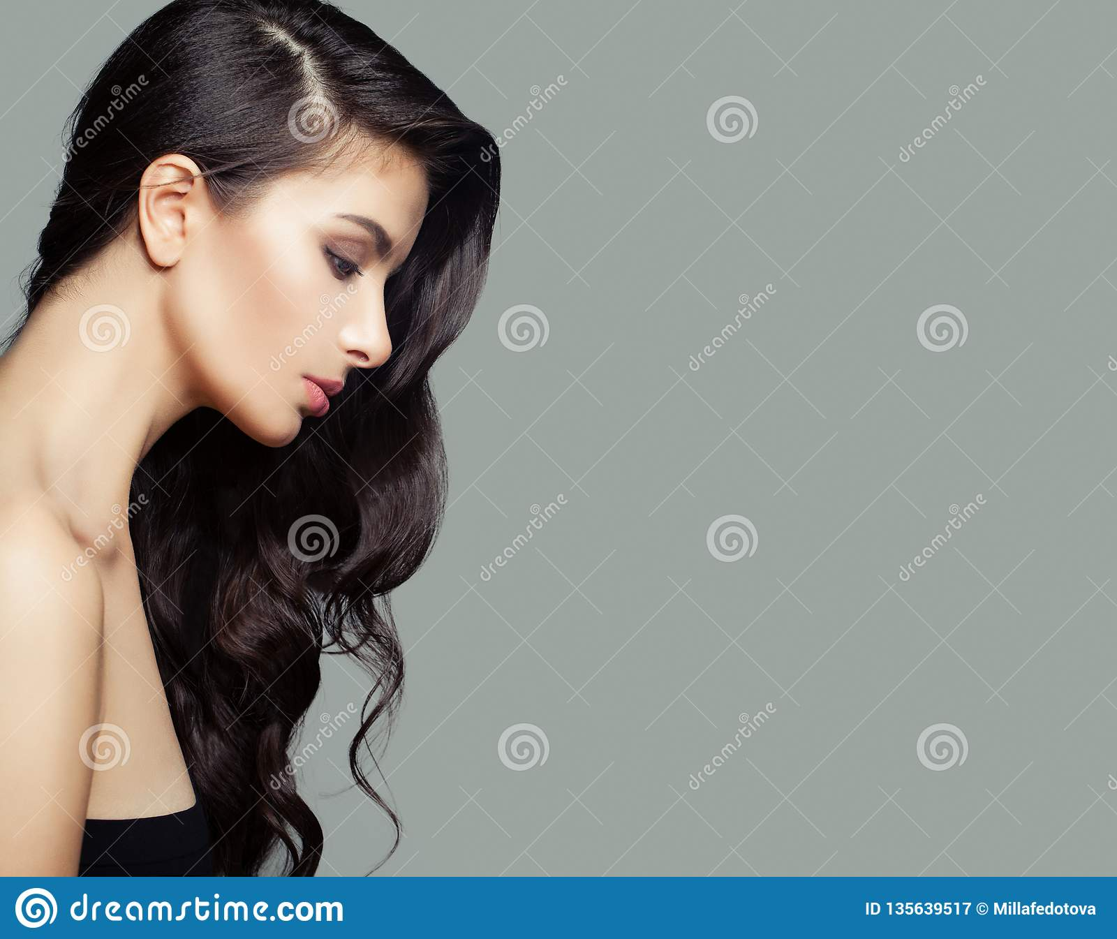 Young brunette woman with long perfect hairstyle. Hair care and beauty salon background