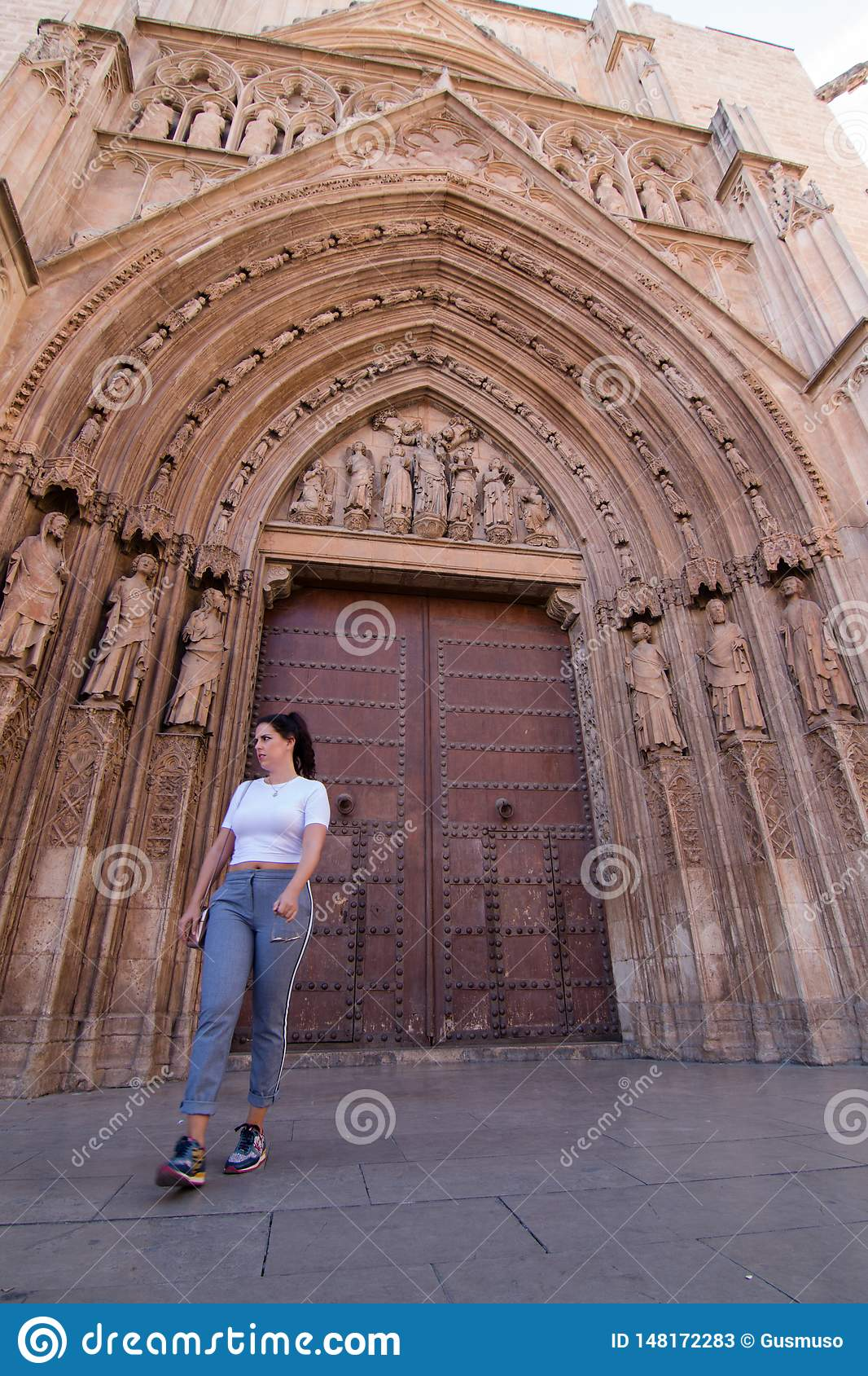 A young brunette woman walking in front of the Cathedral of Valencia Spain with white shirt and gray pants