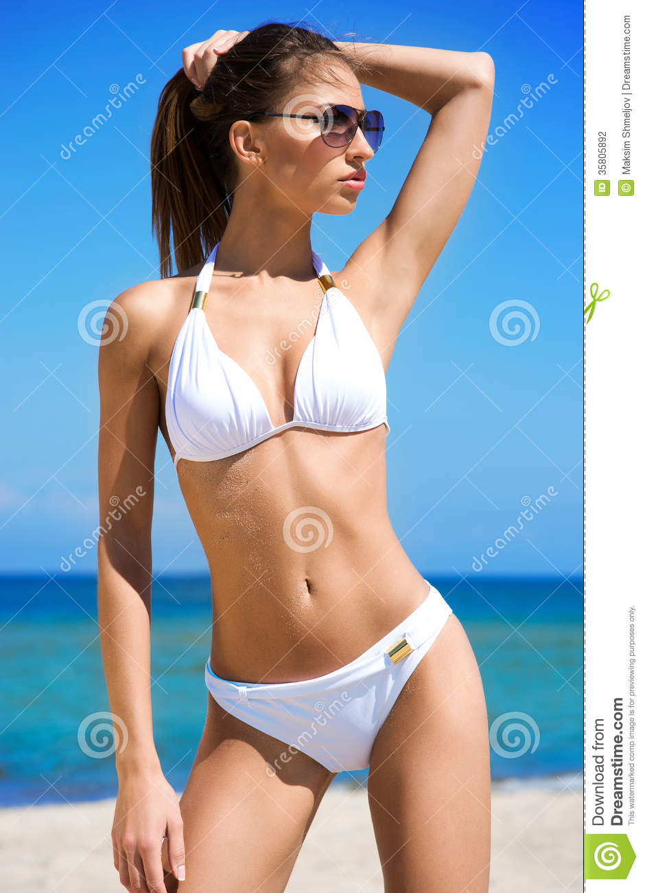 A Young Brunette Woman In A White Swimsuit On The Beach ...