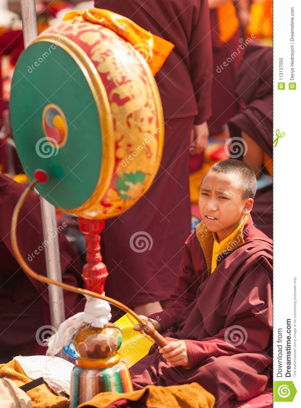 Young buddhist monk with a big ritual drum