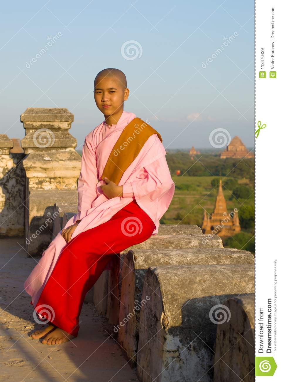 A young Burmese nun girl sits on the parapet of an ancient Buddhist temple