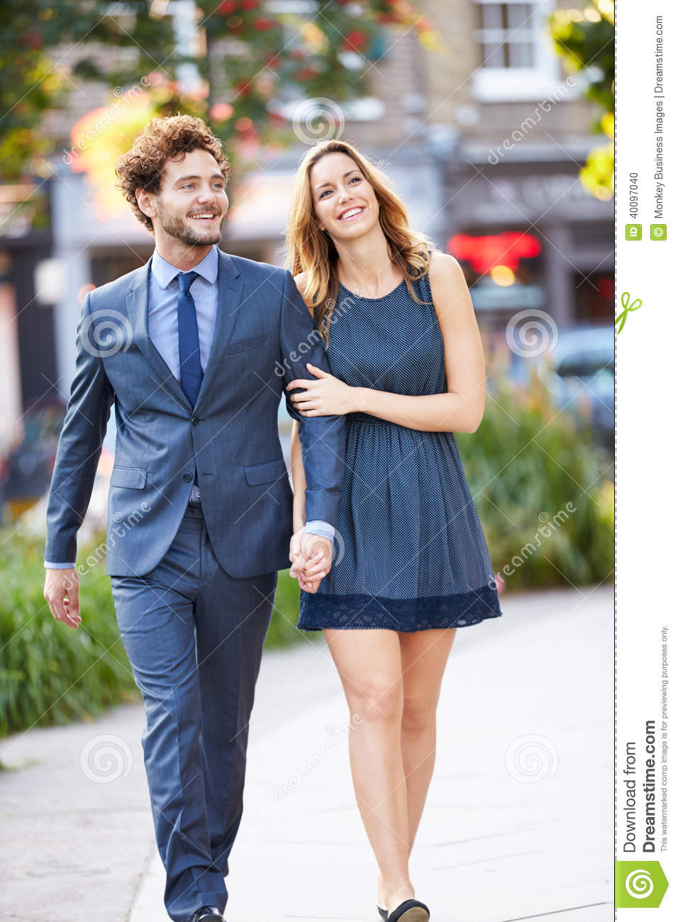 Young Business Couple Walking Through City Park Together