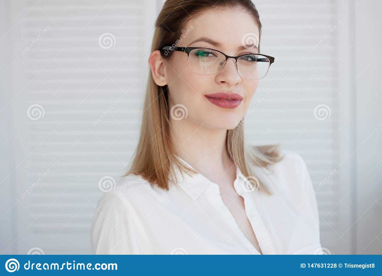 Young business lady in white shirt and glasses. Attractive young woman smiling