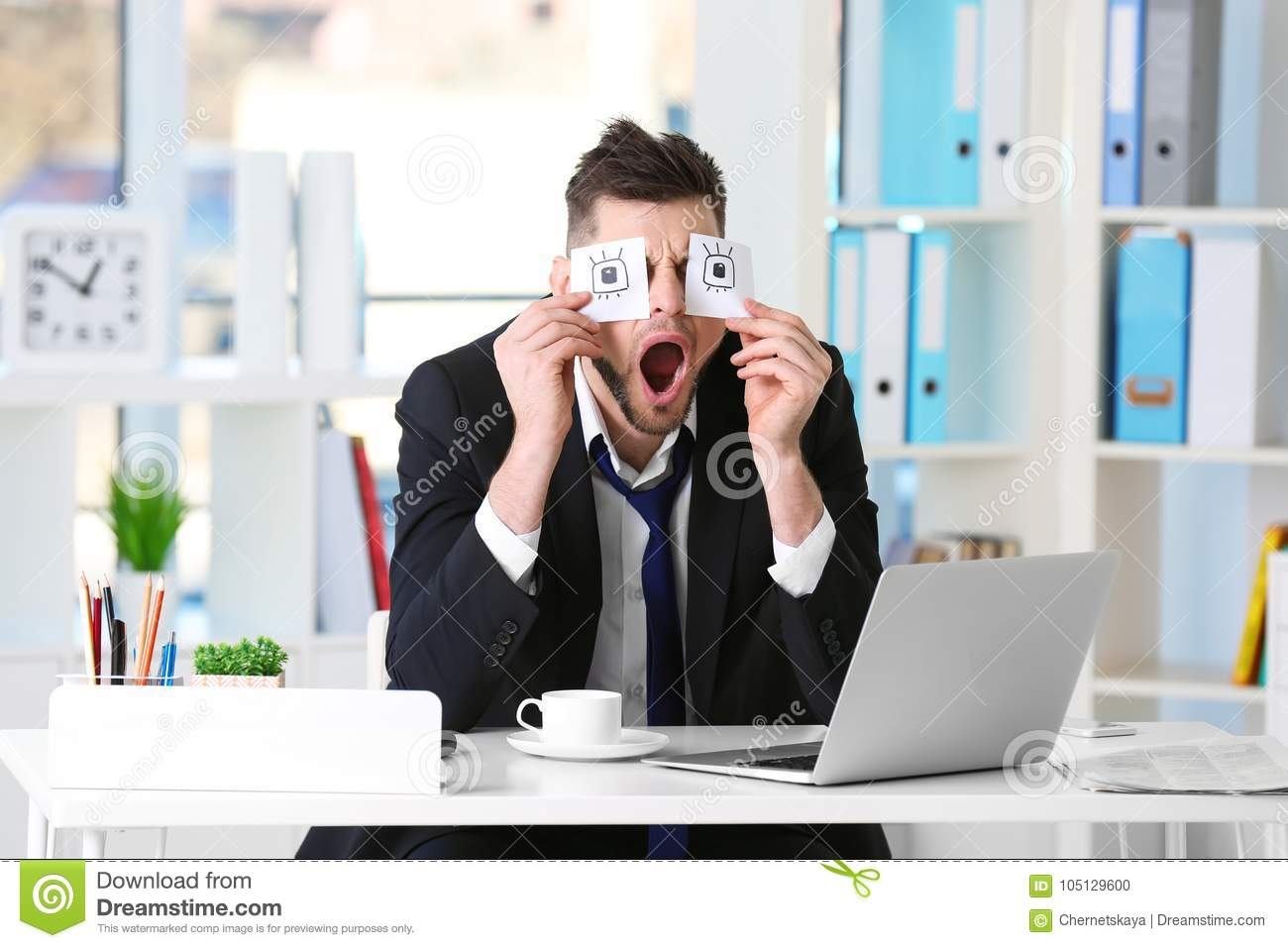 Young Business Man With Fake Eyes Painted On Paper Stickers Yawning