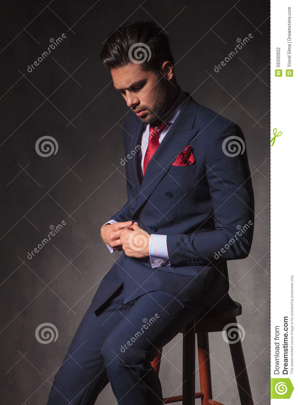 Seated Young Business Man Unbuttoning Jacket Royalty Free