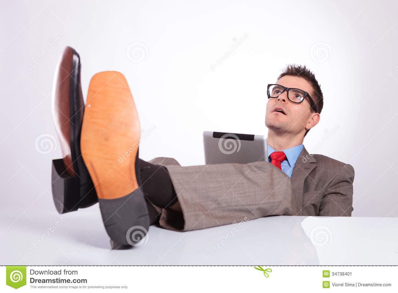 Business Man With Feet On Desk Looks Away Stock Image