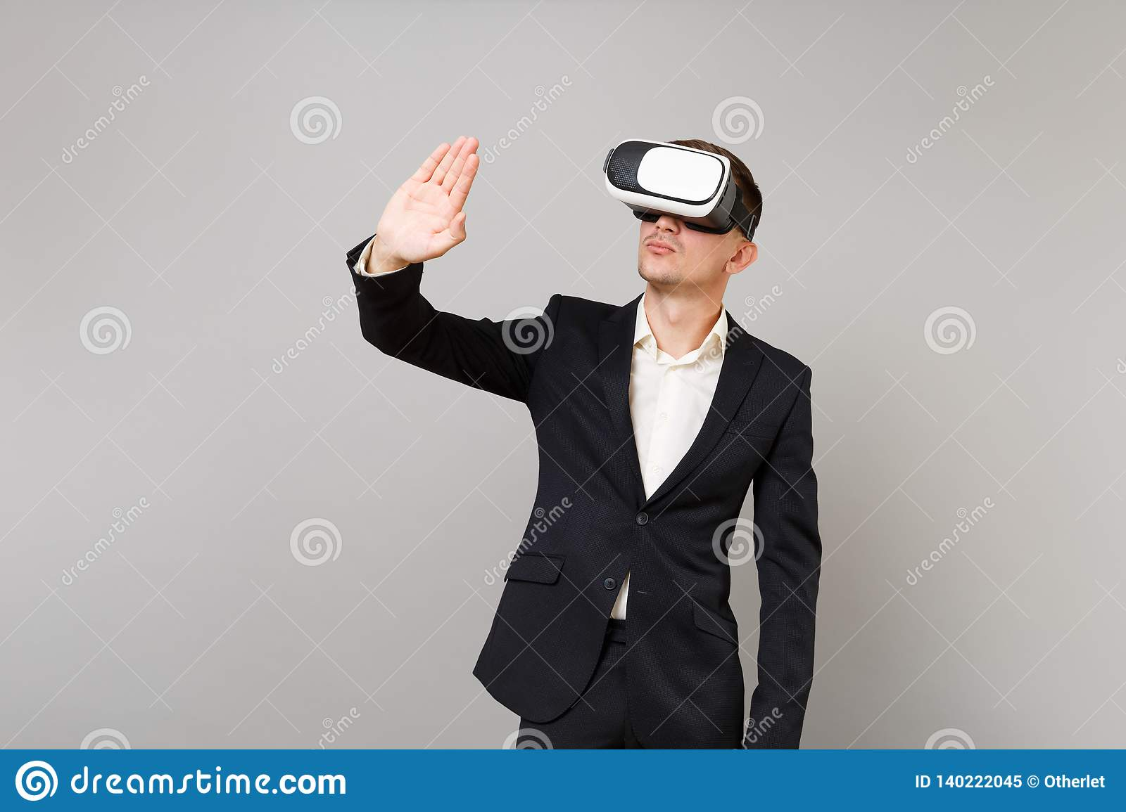 Young business man in suit looking in headset touch something like push click on button and pointing at floating virtual