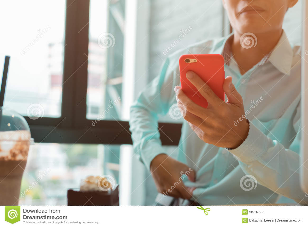 Young business man working in a coffee shop checking his phone