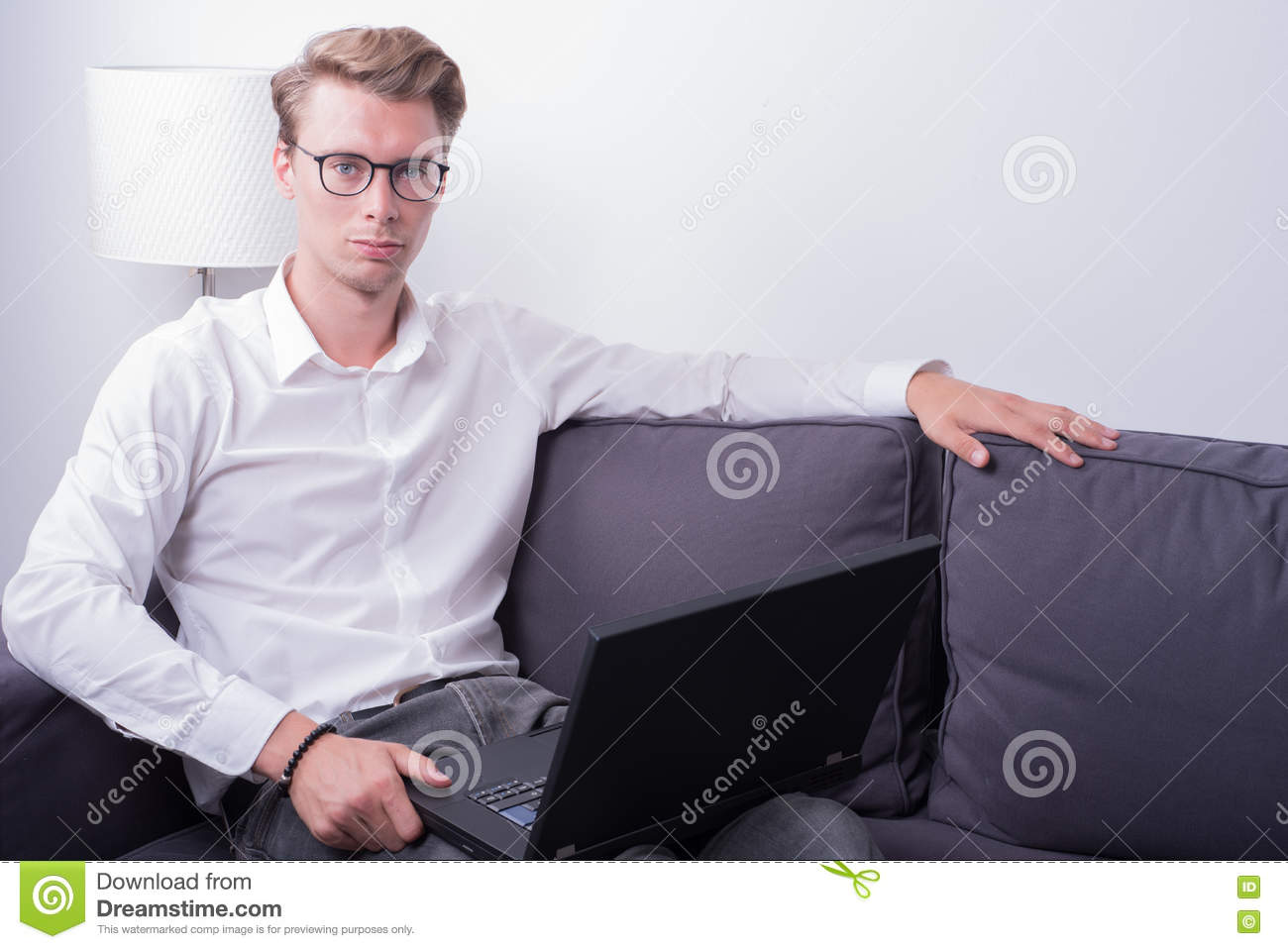 Young business man working at home on couch