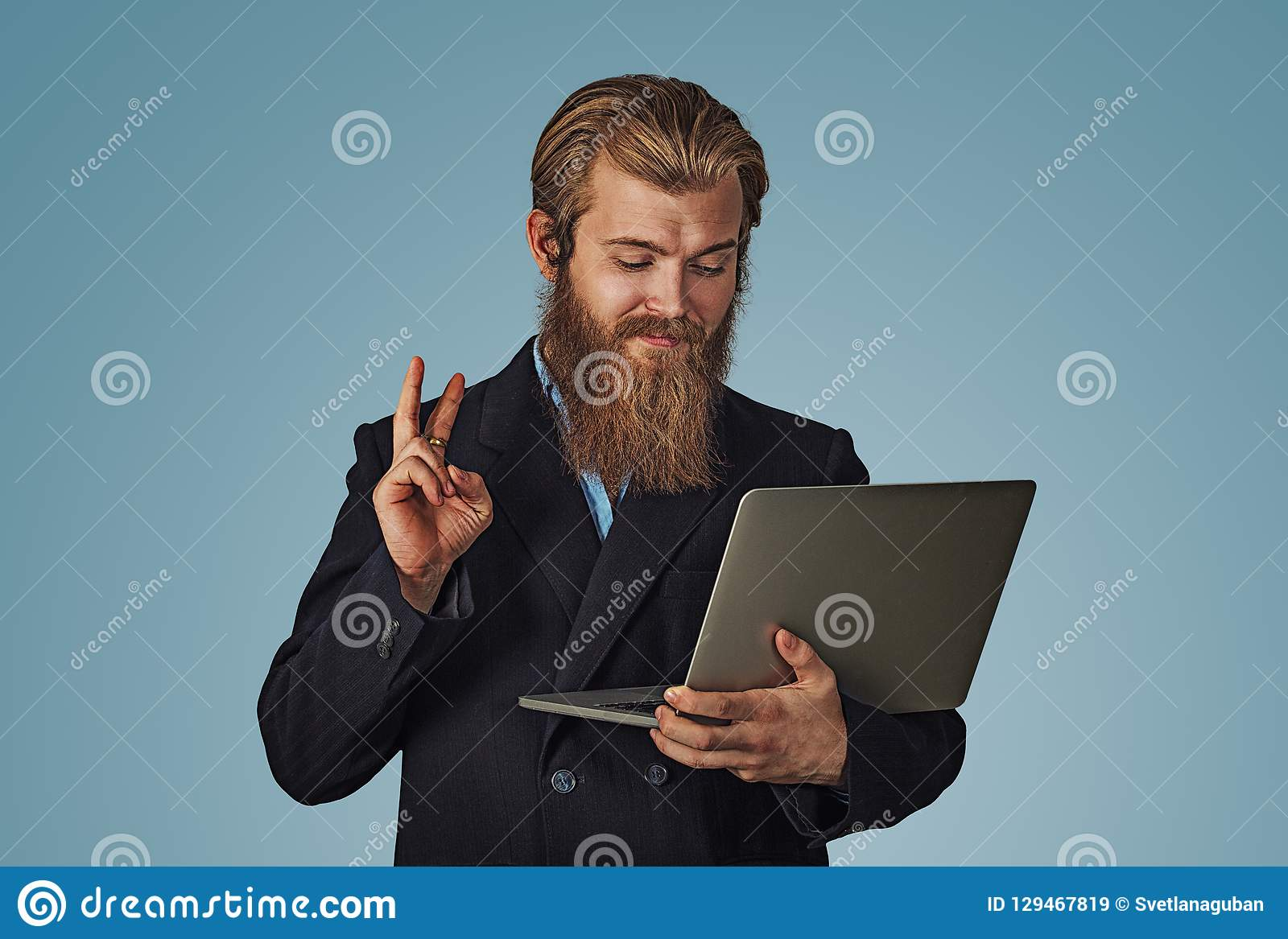 Man working on a laptop giving peace victory hand gesture