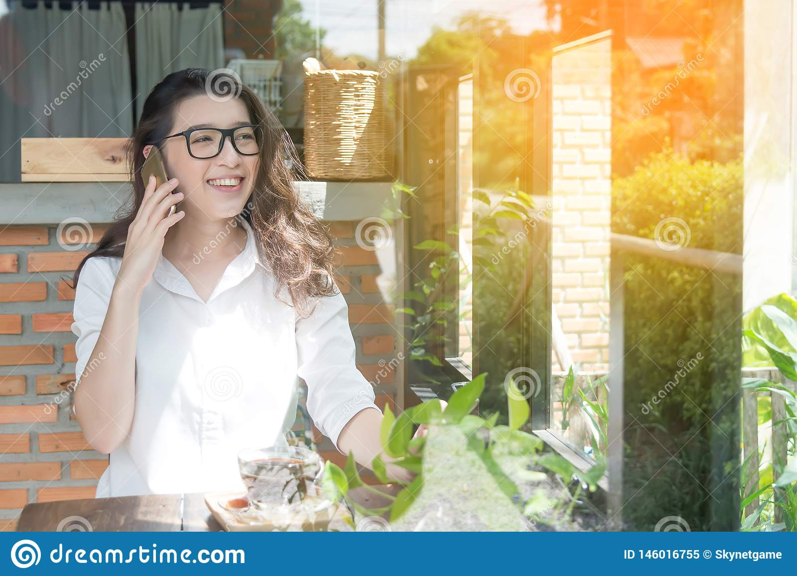 Young business woman cheerful smile sitting at terrace cafe, enjoying online communication using free wireless internet connection