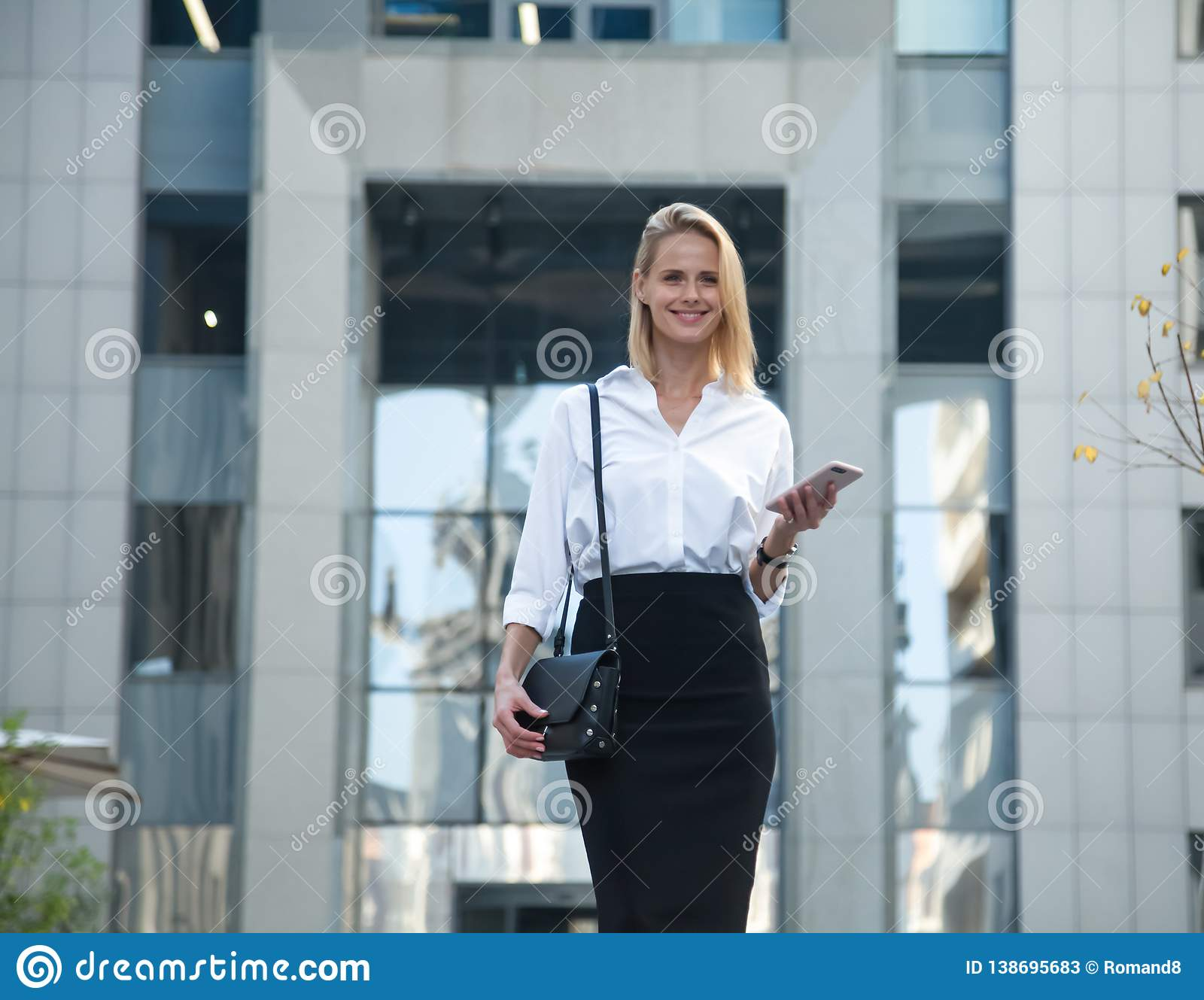 Young business woman in front of office building using her cell phone