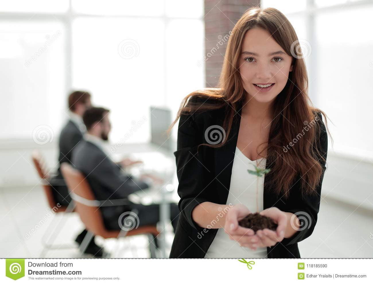 Young business woman holding a fresh sprout