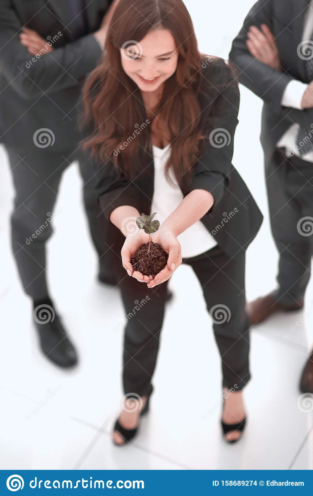 Young business woman showing fresh sprout