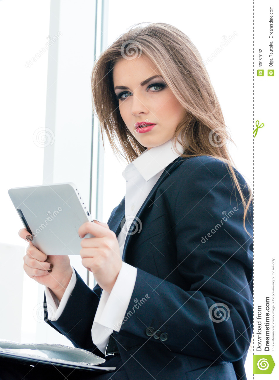 Young business woman using tablet pc while standing relaxed near window at her office stock - Office portrait photography ...