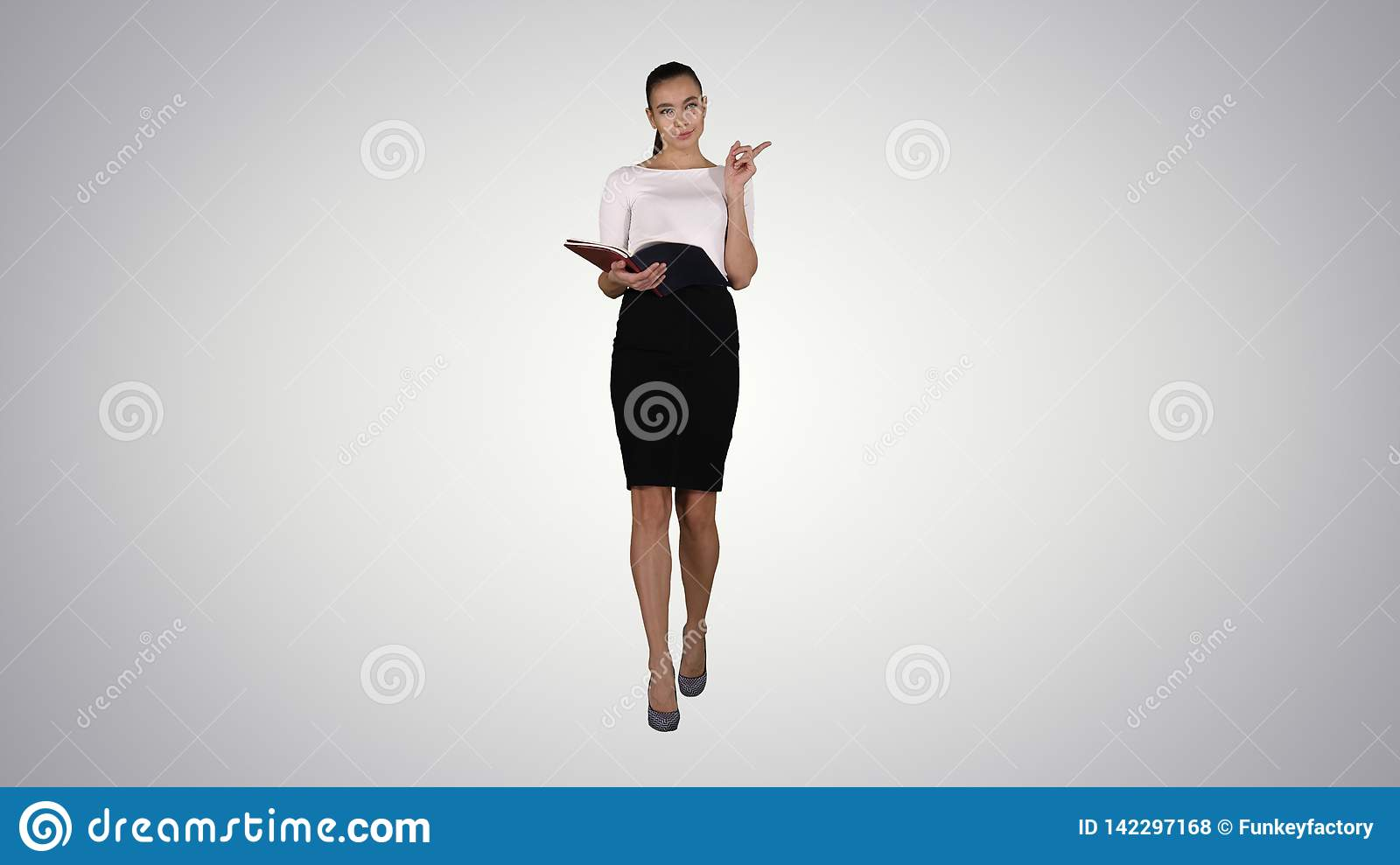 Young business woman walking and reading from notebook on gradient background.