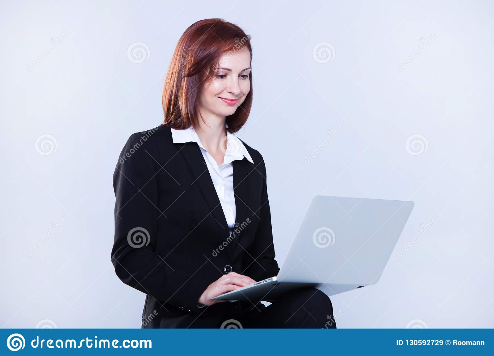 Young business woman working on laptop. Attractive mature businesswoman working on laptop