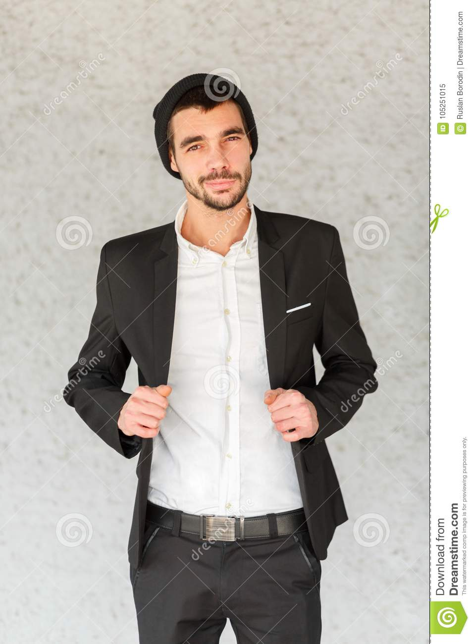 A young businessman adjusts a black suit against a gray background