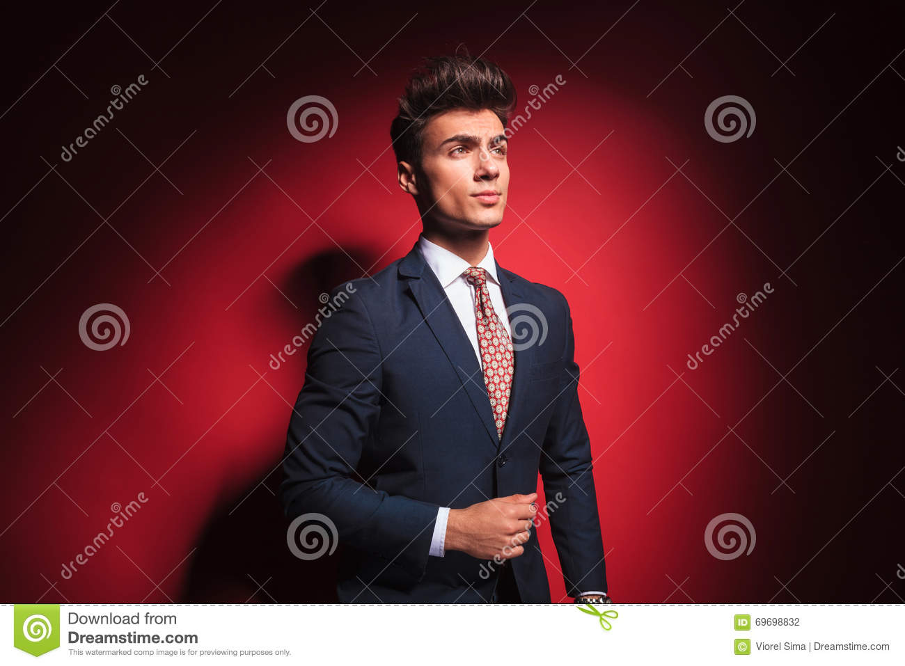 d37529e97290 Portrait of confident young businessman in black suit with red tie posing  arranging his jacket and looking away from the camera in red studio  background