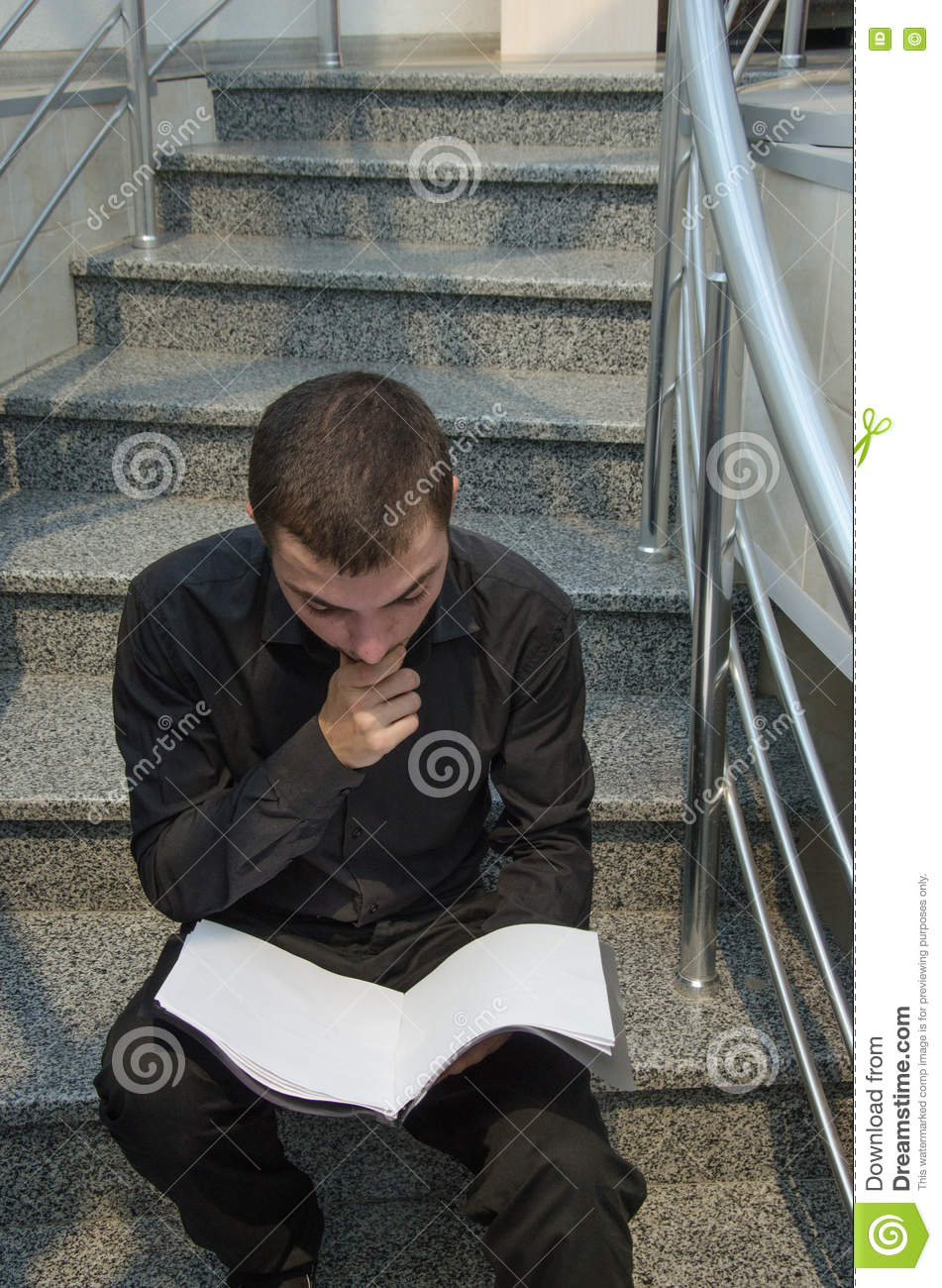 Young businessman in black suit sitting on stairs and reading the documentation papers