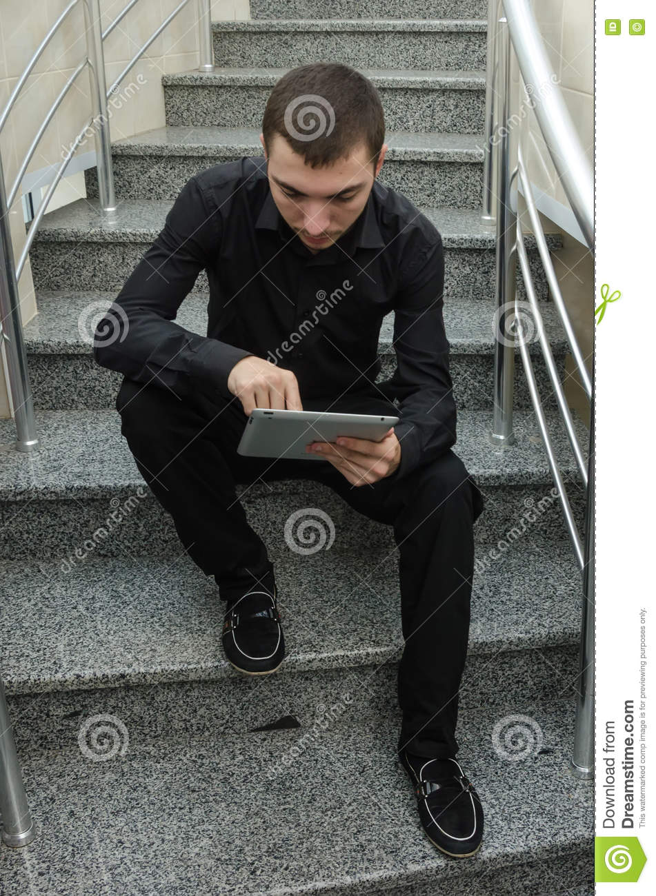 Young businessman in black suit sitting on stairs and reading the documentation papers.
