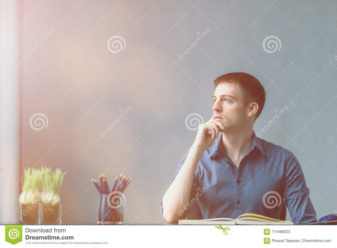 Young businessman caucasians sitting at desk office table and taking notes in notebook. Looking out the window on the left