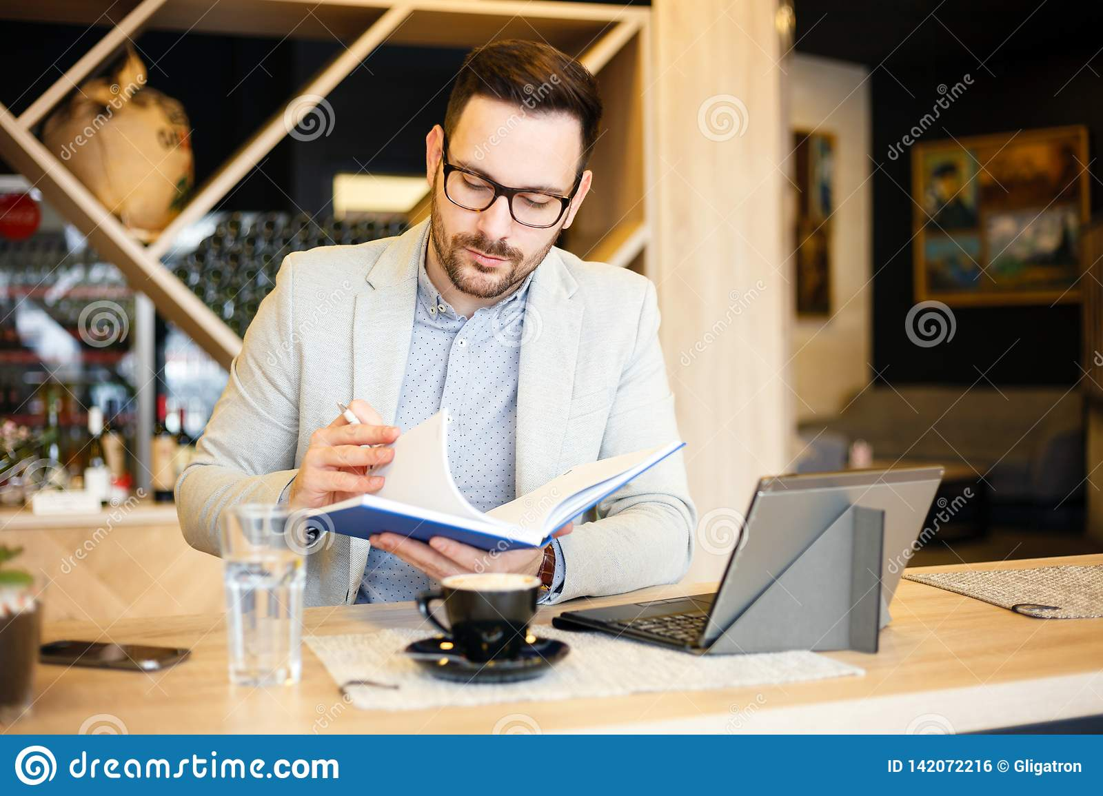 Young businessman checking daily agenda in a notepad while sitting in a modern coffee shop