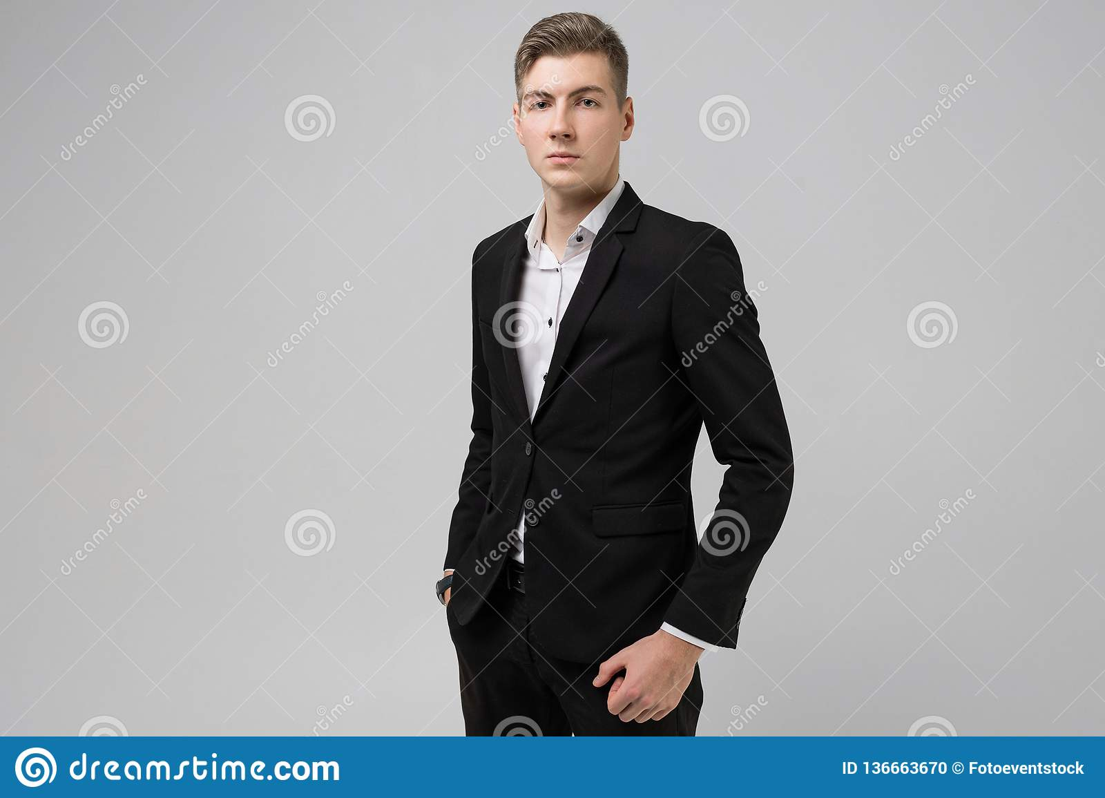 4e0440b37d Portrait of young man with hands in pockets in black suit isolated on white  background