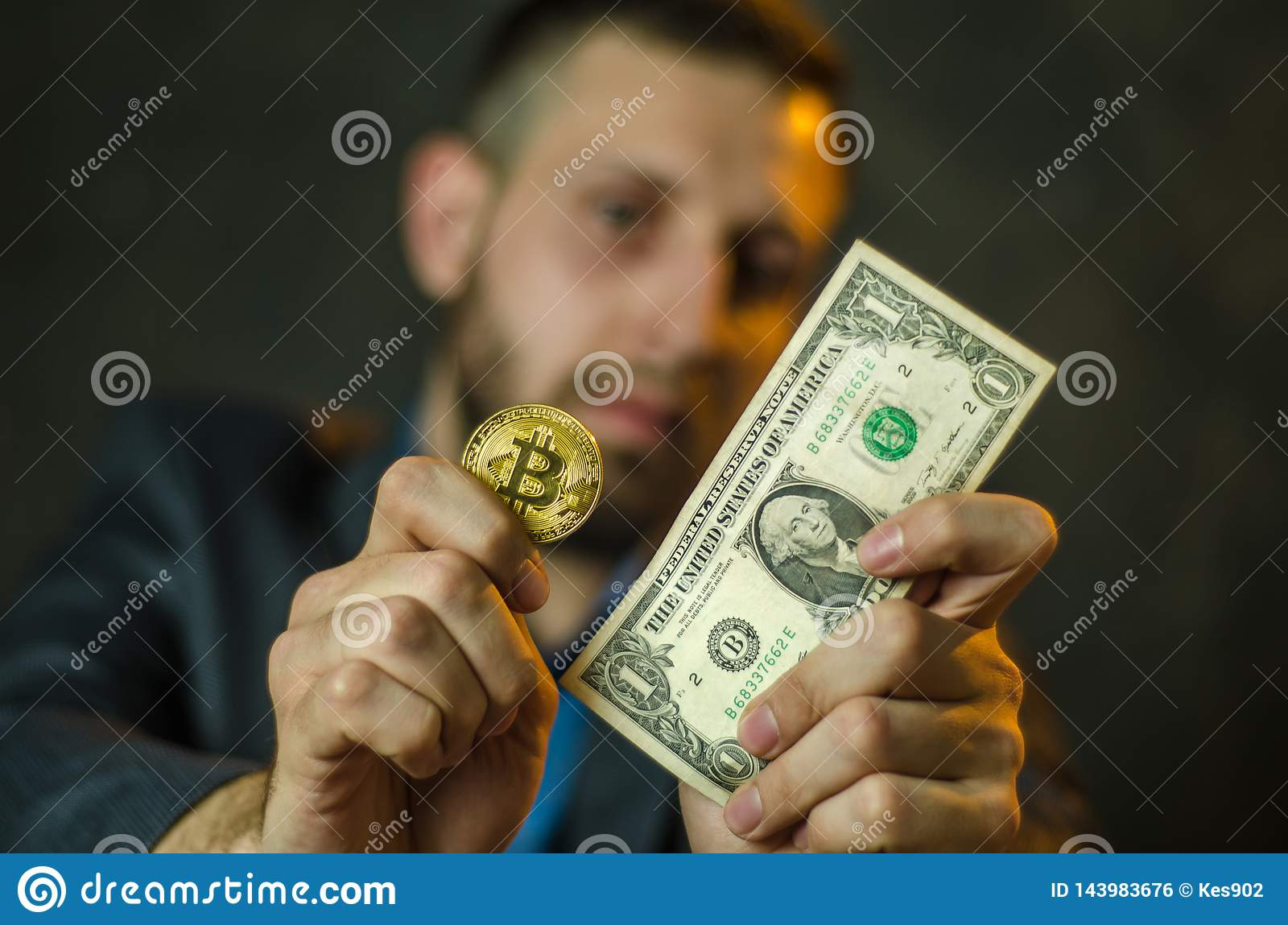 A young businessman holds a coin of bitcoite in his hand