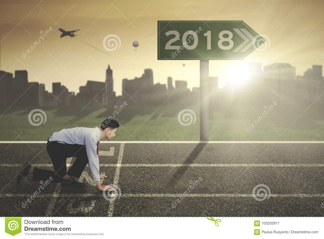 Young businessman with numbers 2018 on the signpost
