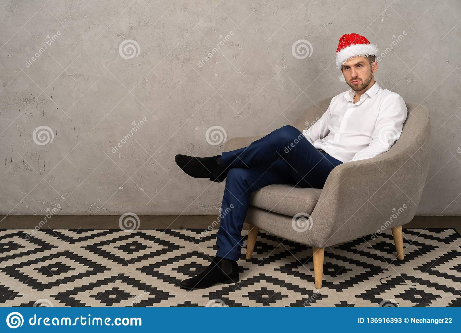 Young businessman sitting on chair in santa hat while boring New Year party in the office
