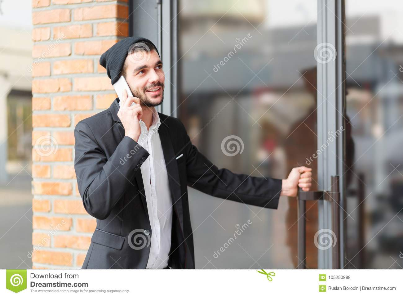 Young businessman speaks on the phone and opens the door of the building