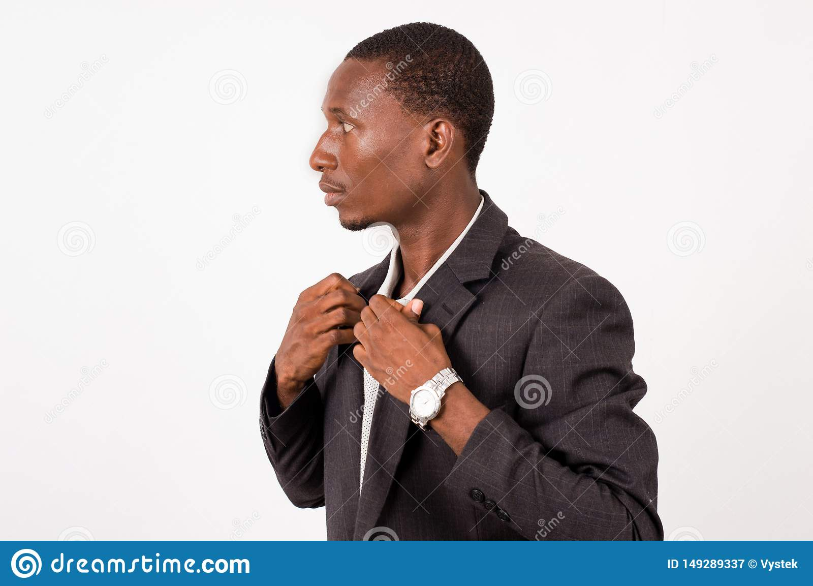 Young businessman standing arranges his shirt glues