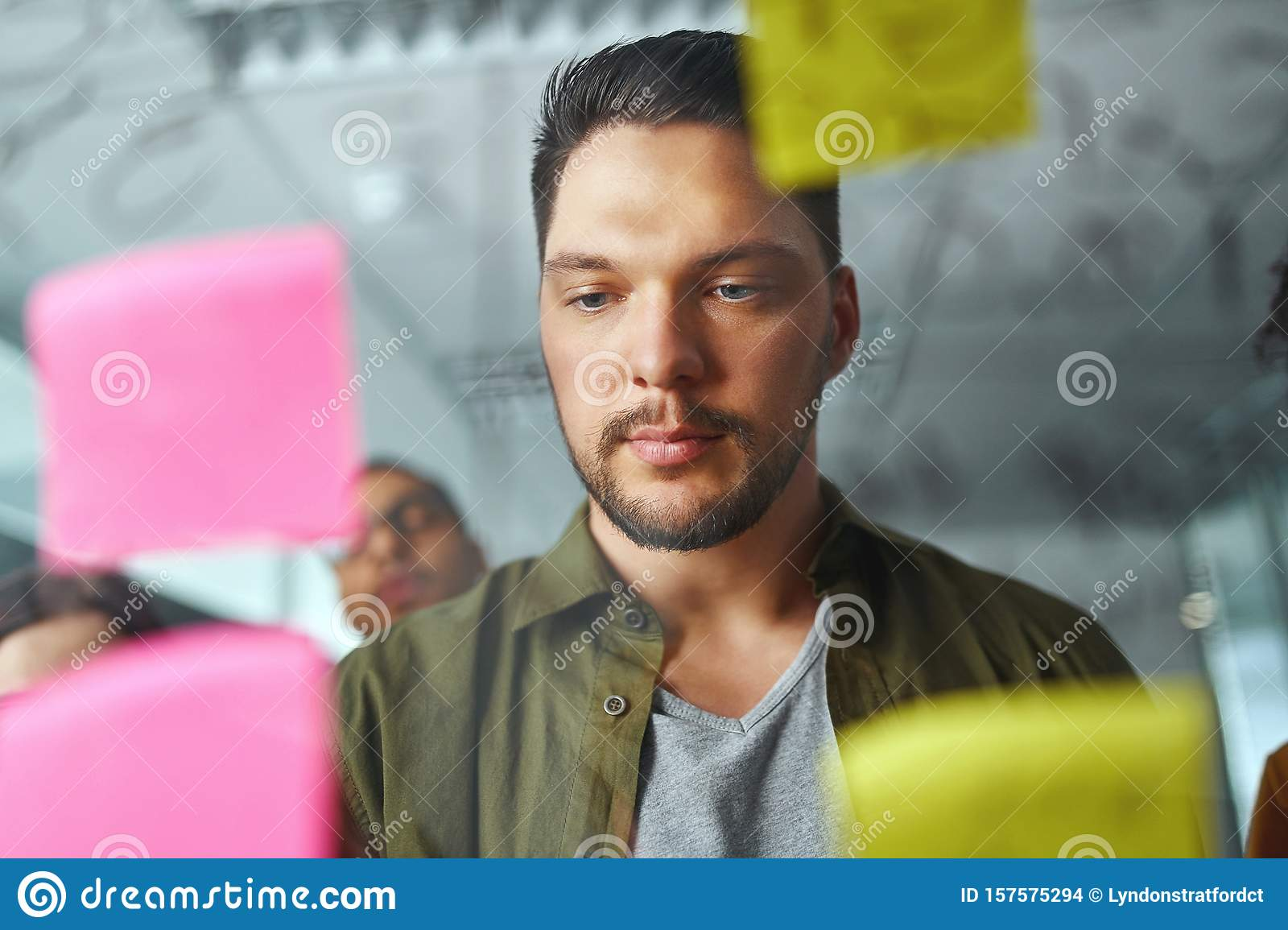 Portrait of a young businessman in casualwear standing behind the transparent glass looking at sticky notes at office