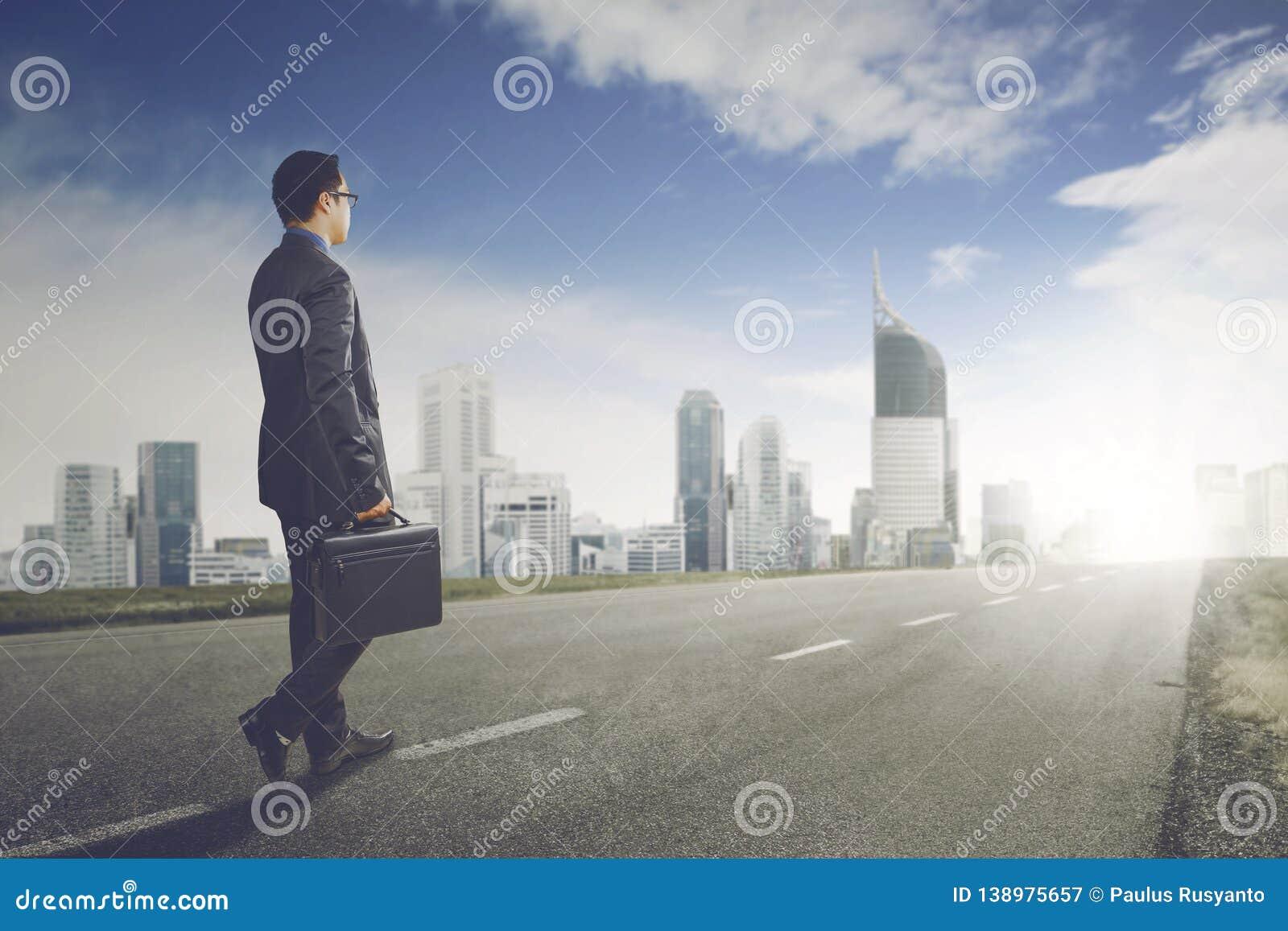 Young businessman walks toward to modern city