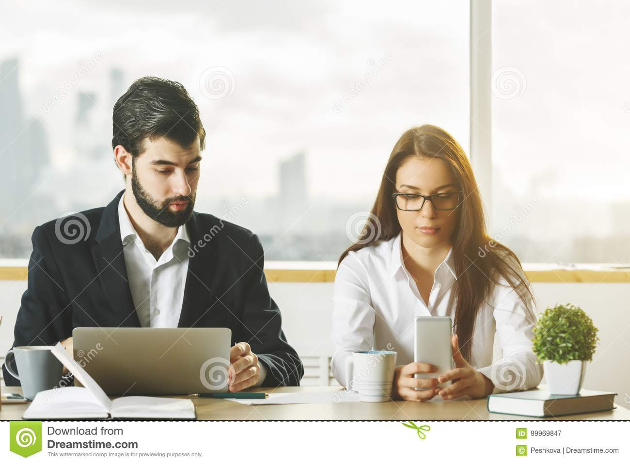 Young businessman and woman using phone