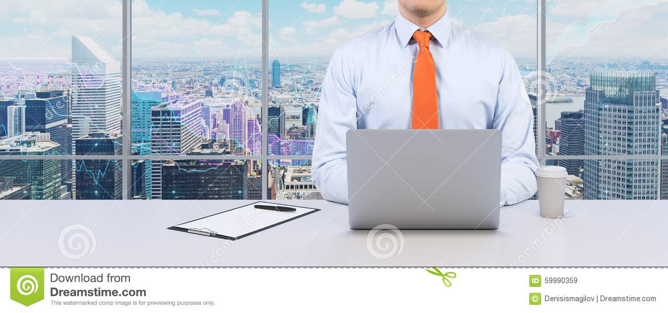 Young businessman is working with the laptop. Modern Panoramic office or work place with New York city view.