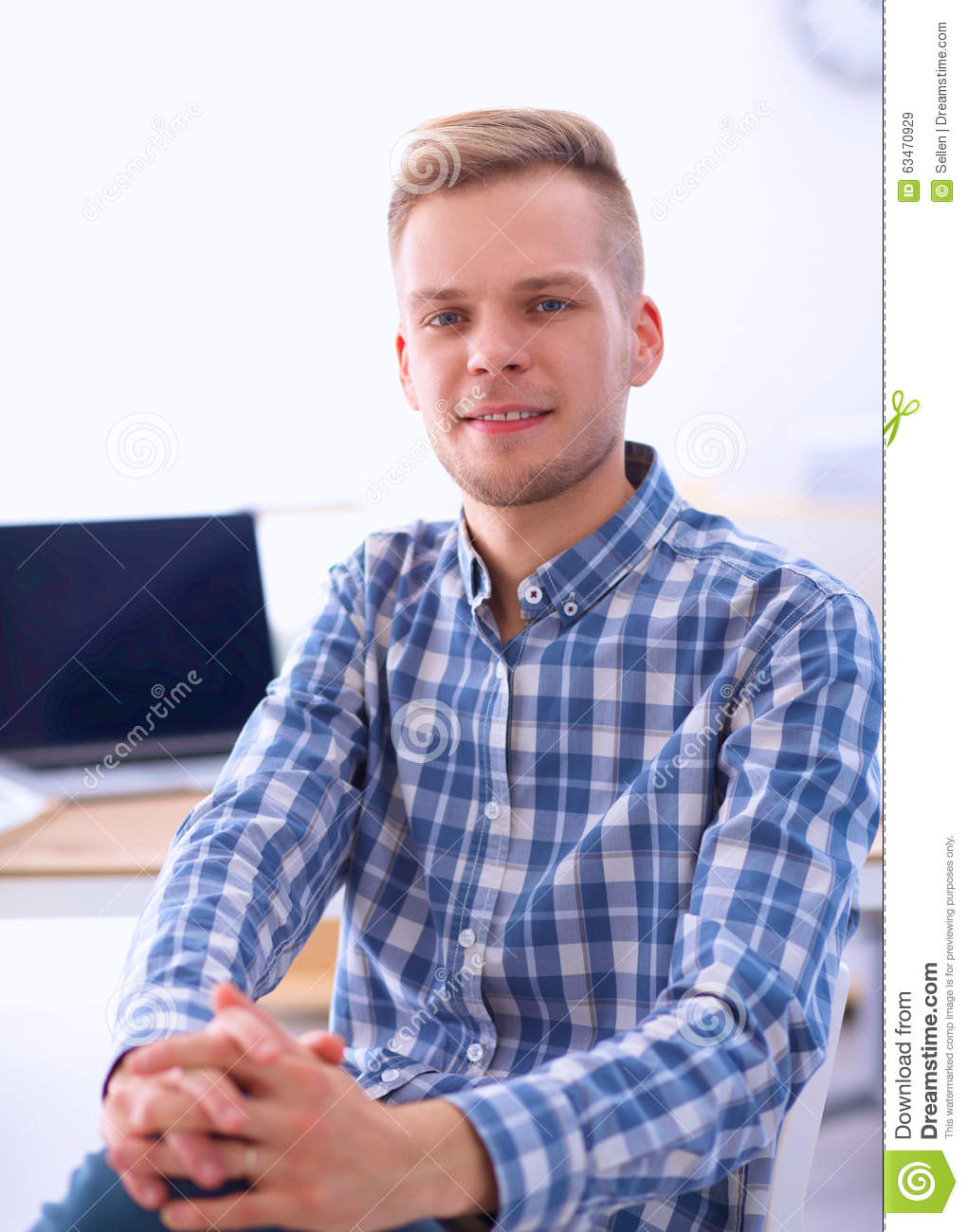 Young businessman working in office, sitting at