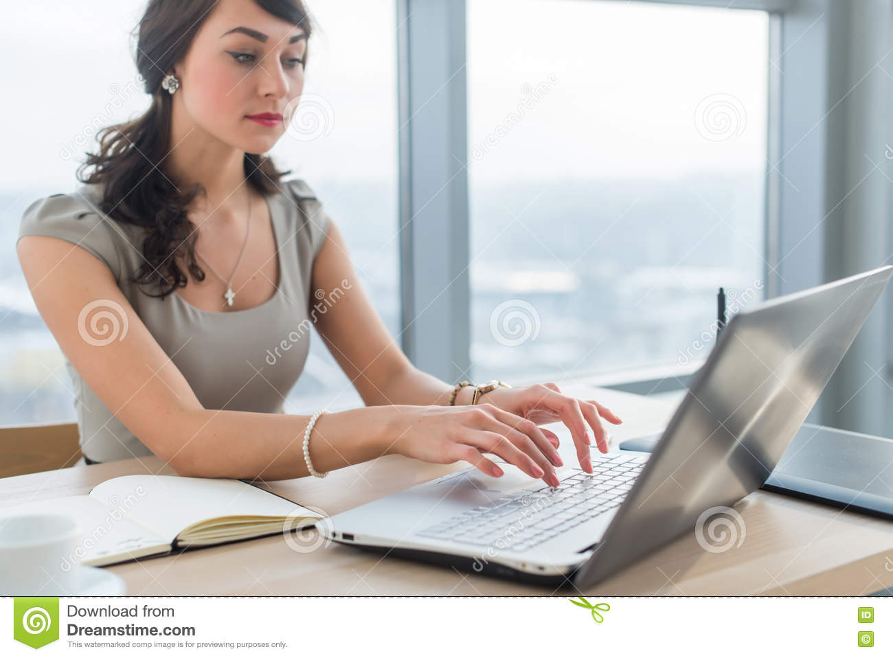 young businessw sitting at work desk reading and typing new e young businessw sitting at work desk reading and typing new e mail using