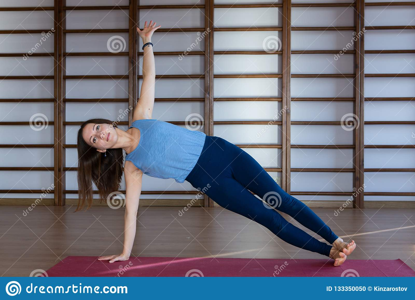 Young calm pretty woman wearing white sportswear working out , doing yoga or pilates exercise. Full length