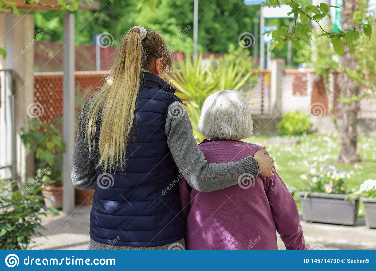 Young carer walking with the elderly woman in the garden